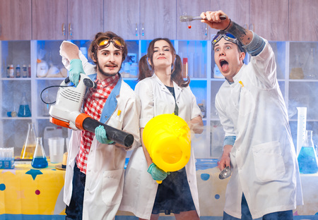 Funny young scientists making experiment in the laboratory together. Archivio Fotografico