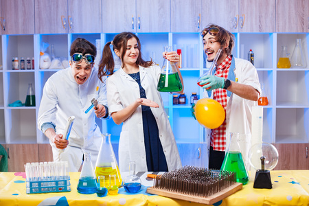 Young funny scientists standing in laboratory and making an experiment.