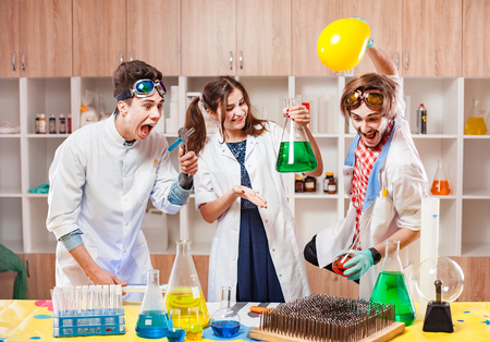 Emotional funny male and female scientists with chemistry equipment in laboratory.