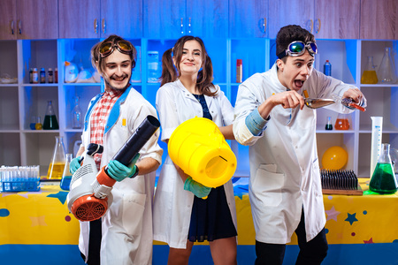 Cheerful young scientists with equipment in modern laboratory.