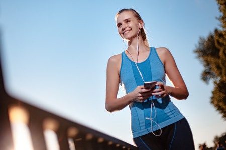 Active and beautiful girl in a blue sports t-shirt, listening to music via the player in the mobile phone touch.