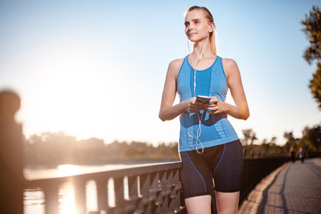 Active and beautiful girl in a blue sports t-shirt and black shorts, listening to music via the player in the mobile phone touch.
