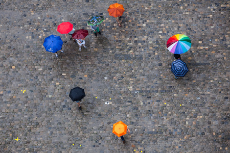 People with different umbrellas on the pavement in the rain. View from above.