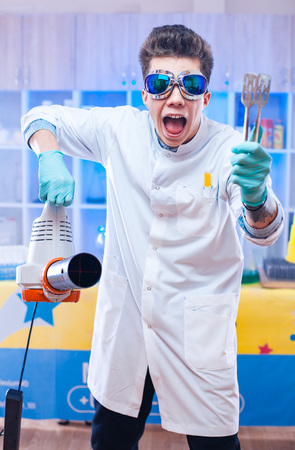Crazy young scientist in blue glasses standing with wind machine in modern laboratory.
