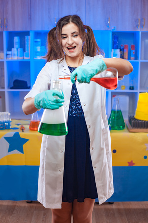 Cheerful excited scientist woman mixing chemistry liquids in flasks in laboratory.