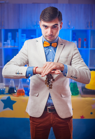 Young magician in stylish suit standing with coins and looking at camera in the laboratory.