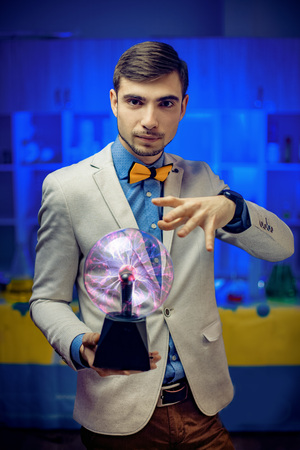 Young man in suit holding hand over plasma sphere in science lab. Archivio Fotografico