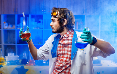 Young crazy scientist with two flasks in blue illuminated lab. Archivio Fotografico