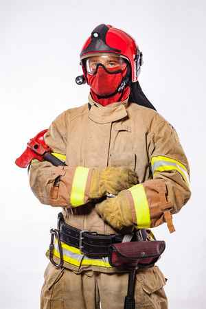 Anonymous firefighter wearing helmet and protective suit holding ax and looking at camera on white. Archivio Fotografico