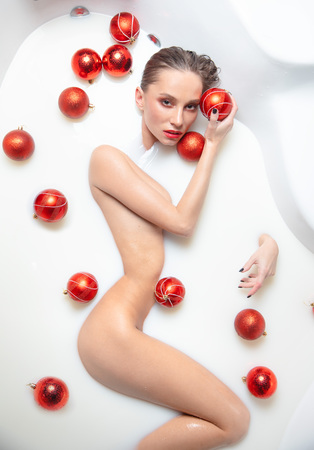 Bath with milk. Christmas theme. Spa. Girl in milk, with Christmas toys.