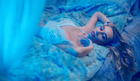 The girl is lying on the bed in the blue room. She has white underwear, makeup and beautiful hair.