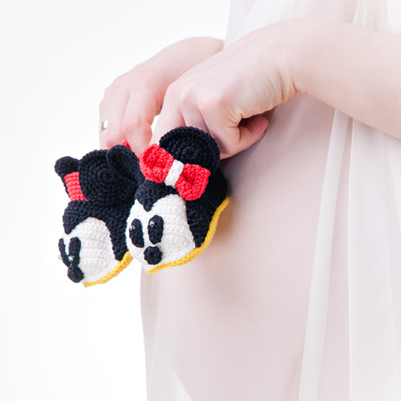 Booties in the form of a minni mouse in the hands on the abdomen of a pregnant woman