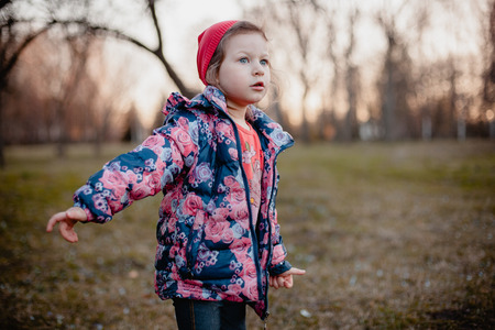 A little girl in a blue jacket with roses and in a red cap is looking into the distance.