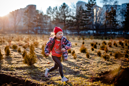 A little girl in a blue jacket with roses, in a red cap and in jeans is runnig around the park.