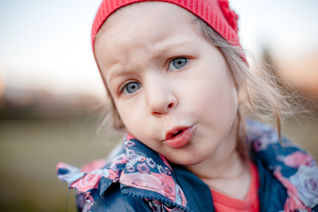 Portrait of a little girl in a blue jacket with rose and in a red cap with emotion