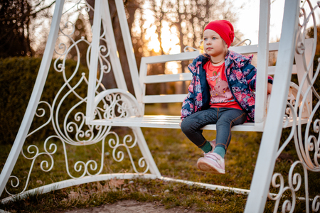 A little girl in a blue jacket with roses, in a red cap and in jeans is riding on white swings. Archivio Fotografico