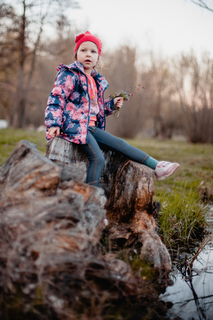 A little girl in a blue jacket with roses and in a red cap is sitting on a stump by the stream with a bouquet of flowers in her hands.