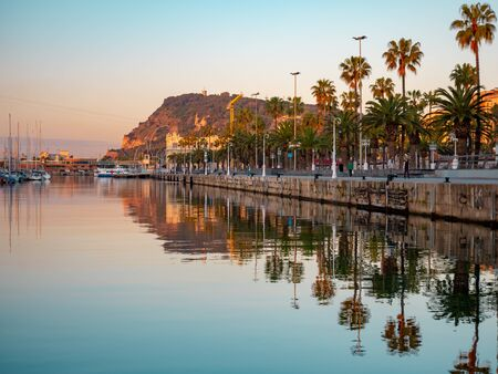 View of a promenade passing Port Vell in Barcelona during the sunrise. Stock Photo