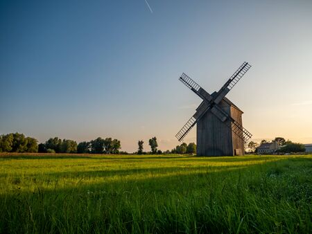 Old windmill on the green field. Фото со стока