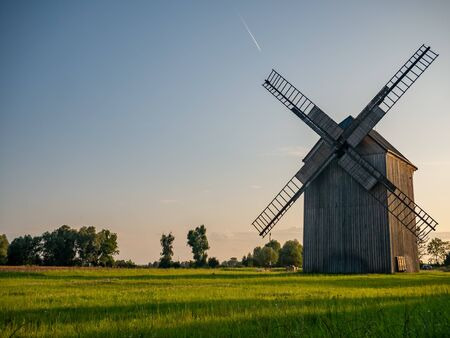 Old windmill on the green field.