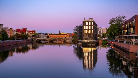 The river Odra at sunrise with modern building in Wroclaw, Poland. Viwe from university bridge.