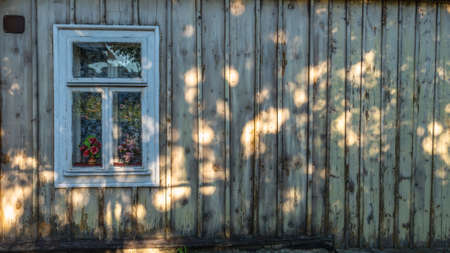 Rustic window in wooden village cottage house.