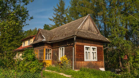 Traditional wooden mountain house on green field in Pieniny Mountains, Poland.