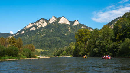 Traditional rafting on the Dunajec Gorge and view of Three Crowns Massif, Pieniny, Poland.