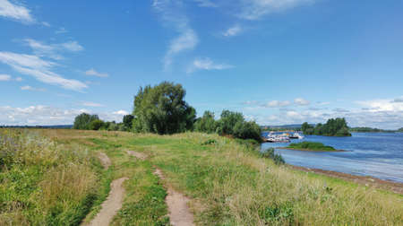sunny landscape with a river and a green shore against a blue sky with clouds
