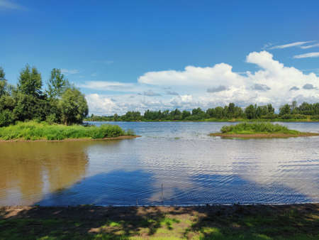green islets on the river against the background of blue sky with clouds on a sunny day