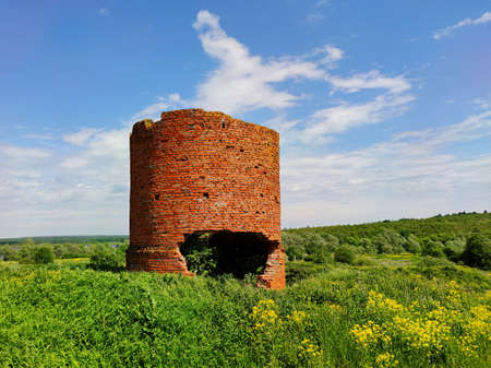 the old ruined red brick tower seems to open its mouth among a beautiful green field against a blue sky with clouds on a sunny day