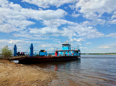 an empty ferry near the riverbank is waiting for passengers and transport on the background of a beautiful blue sky with clouds on a sunny day