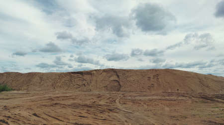 sand quarry against blue cloudy sky in panoramic scene