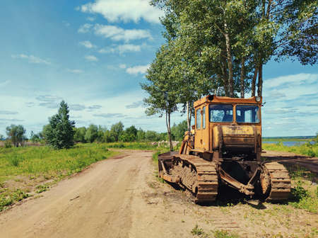 yellow tractor bulldozer stands on the side of a country road in the village against a beautiful blue sky on a sunny day Standard-Bild