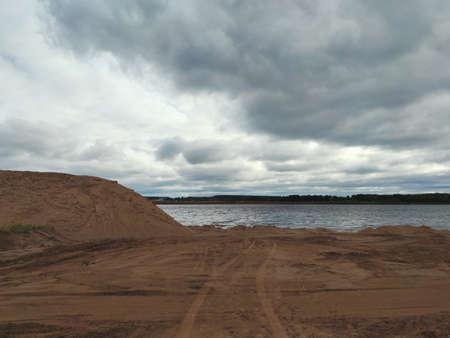 sandy coastal landscape against stormy cloudy sky