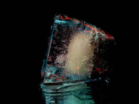 a piece of ice like an inverted glass with dangerous alcoholics in a creative and abstract photo Stock fotó