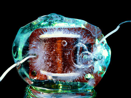 the electric coil of the transformer frozen in ice and illuminated in the dark with green light symbolizes the technological theme Stock fotó