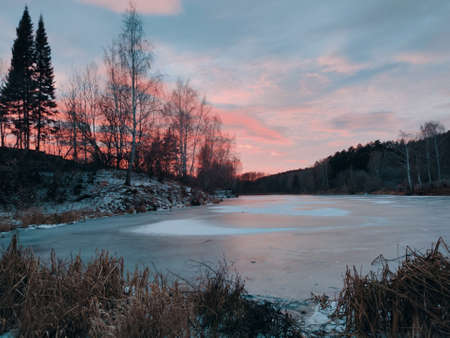 frozen pond near the forest against the background of a crimson sunset in the evening landscape