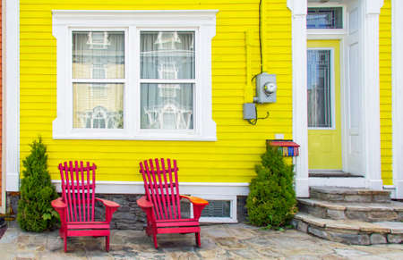 front house: Bright, yellow house with two red-orange adirondack chairs in front.