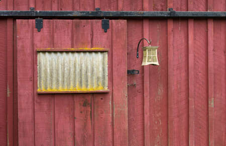 鉄の据え付け品と風化の赤い納屋の扉 写真素材