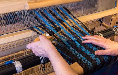 hand woven: Woman weaving a wool scarf on a floor loom.