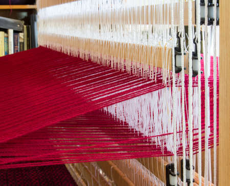 The white string heddles separate the red warp threads on this loom photo