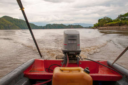 Old outboard motor with its gasoline canister close by in a river in Colombia