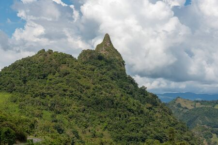 Peak of a mountain near dirt road in the foresta of the Colombian countryside on a sunny day. Colombia