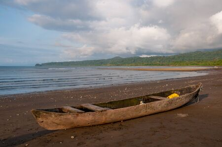 Rustic fishing boat made from the trunk of a trees on a beach on the pacific coast of Colombia.
