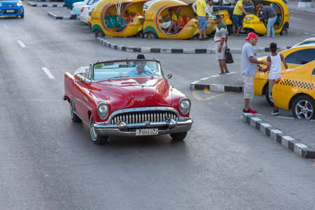 Classic taxi from Old Havana passing through Cocotaxi's parking lot, which are used by tourists who visit the island of Cuba. Havana Cuba. January 2, 2019 写真素材 - 150565298