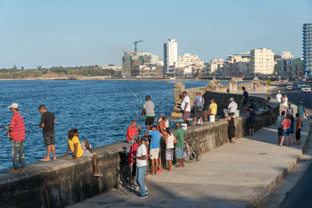Daily life in the wall of the avenue of El Malecon where fishermen and friends meet during the day. Havana. Cuba. January 2, 2019