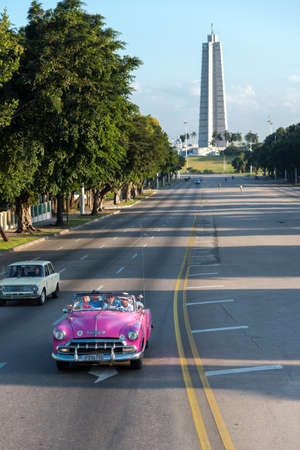 Pink taxi with tourists on the avenue that leads to the Palza de la Revolucion one of the most visited places in the city. Havana. Cuba. January 2, 2019