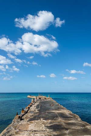 Old pier over blue sea. Havana. Cuba.