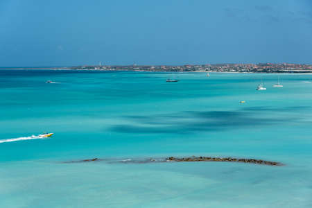 Fast motorboat crossing a beach in aruba surrounded by a reef visible on the surface. Palm Beach. Aruba February 24, 2019 Фото со стока - 150492064
